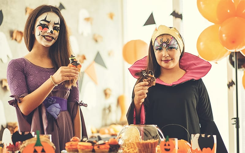 Teenagers toasting in costumes on Halloween