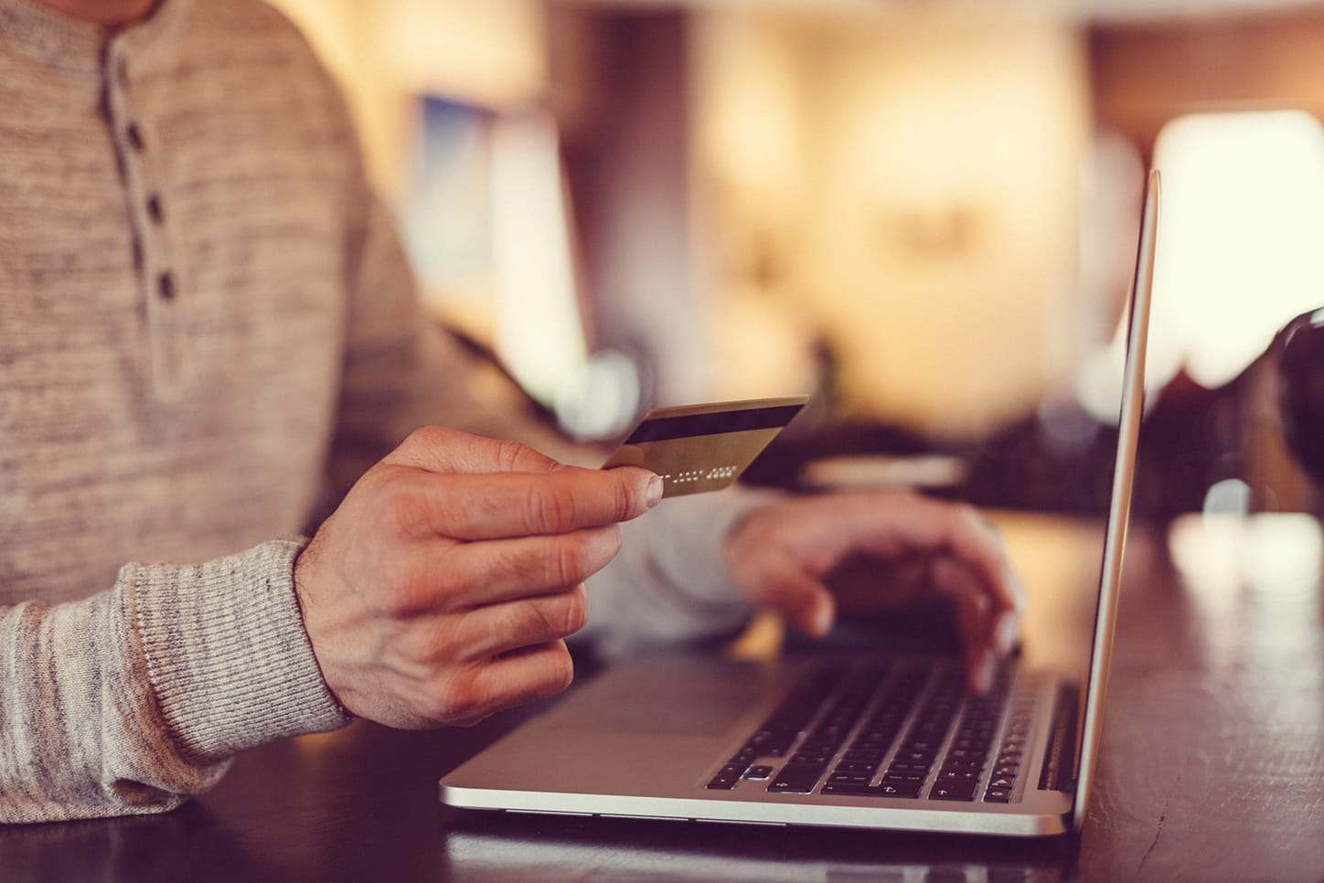 credit card in hand while typing on a laptop computer