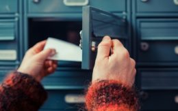 woman's hand as she is getting her post out of her letterbox