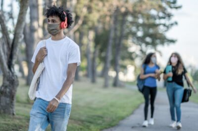 students walking on college campus while wearing masks