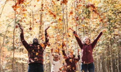 family throwing leaves up in the woods