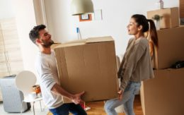 young man and woman moving a box together