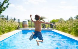 boy jumping into a pool