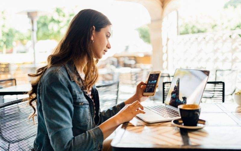 woman working on phone and laptop from coffeeshop