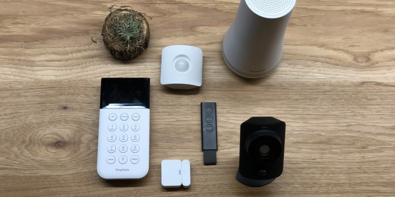 SimpliSafe keypad, entry sensor, motion sensor, key fob, base station, and simplicam on wooden surface