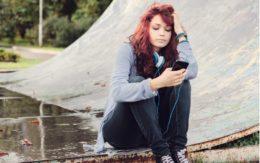 teenager texting at skate park