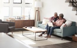 older couple sitting on couch with computer
