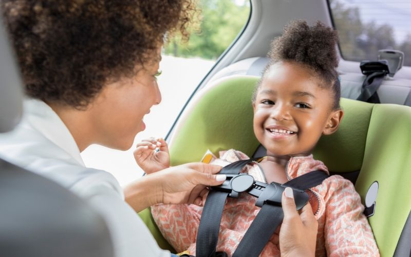 mom buckling in daughter in car seat