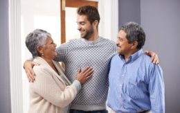 adult man smiling with elderly parents