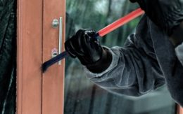 thief entering home with a crowbar