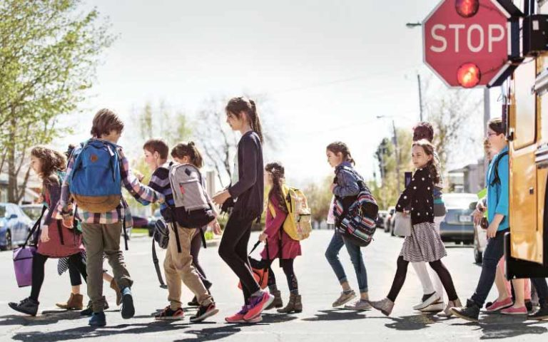 Young children exiting school bus and crossing street