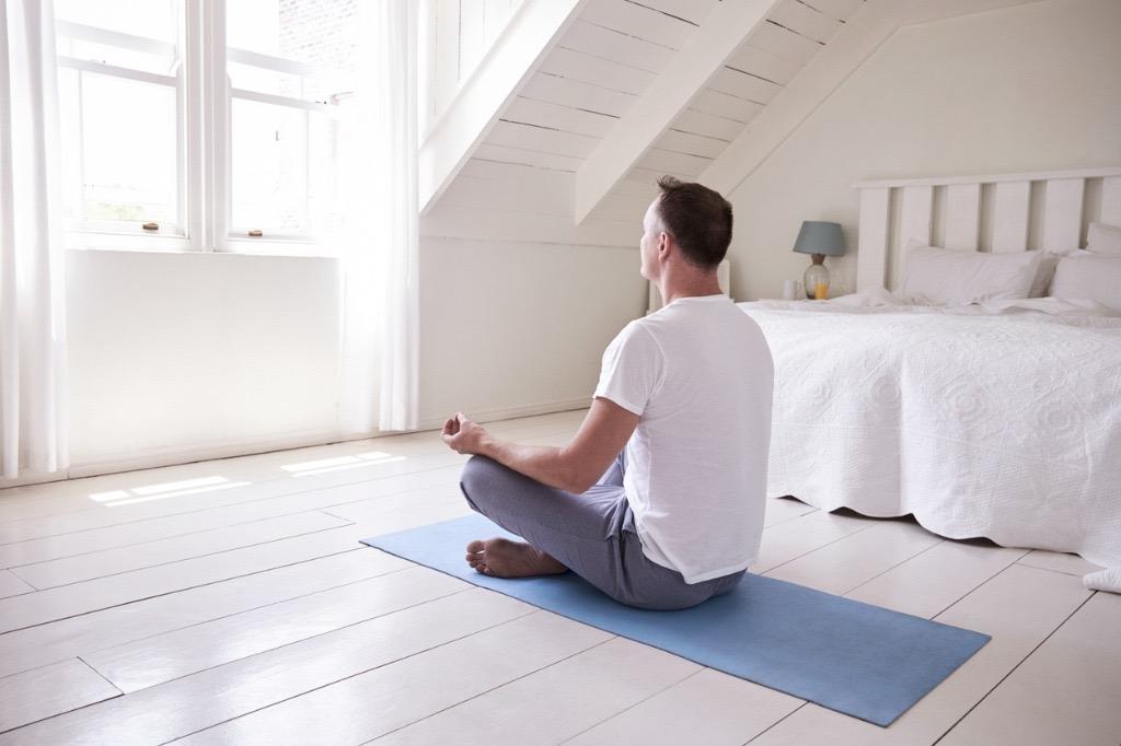 man meditating in bedroom