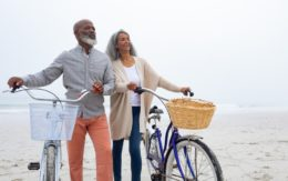 older couple with bicycles on the beach