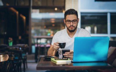 man working on laptop in coffee shop
