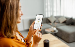 woman checking on home security system via app on smartphone