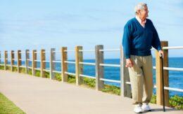senior man walking by the ocean