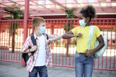 kids at school with masks on and doing an elbow bump