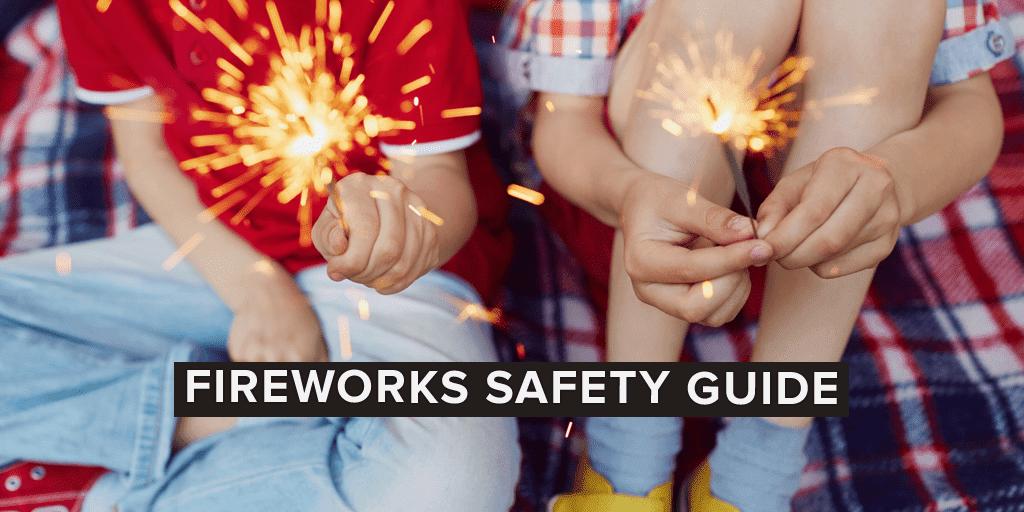 2 kids on a plaid blanket holding sparklers