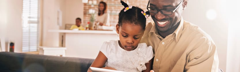 African American family, father and daughter looking at tablet