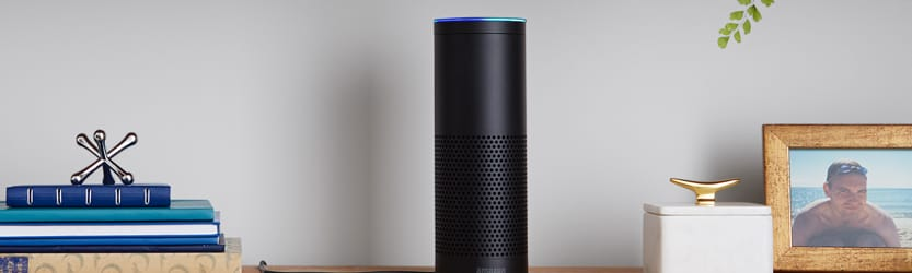 Amazon Echo on shelf with books, photos