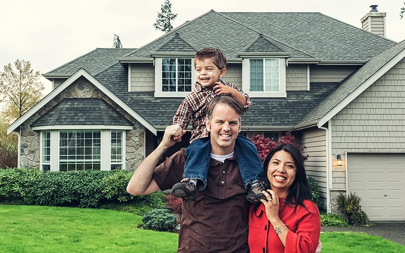 husband, wife, and son standing in front of house