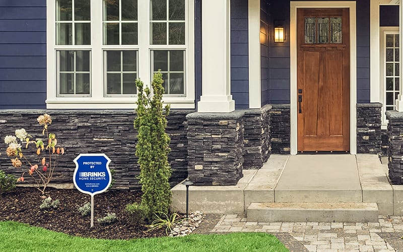 brinks security sign in front of blue house