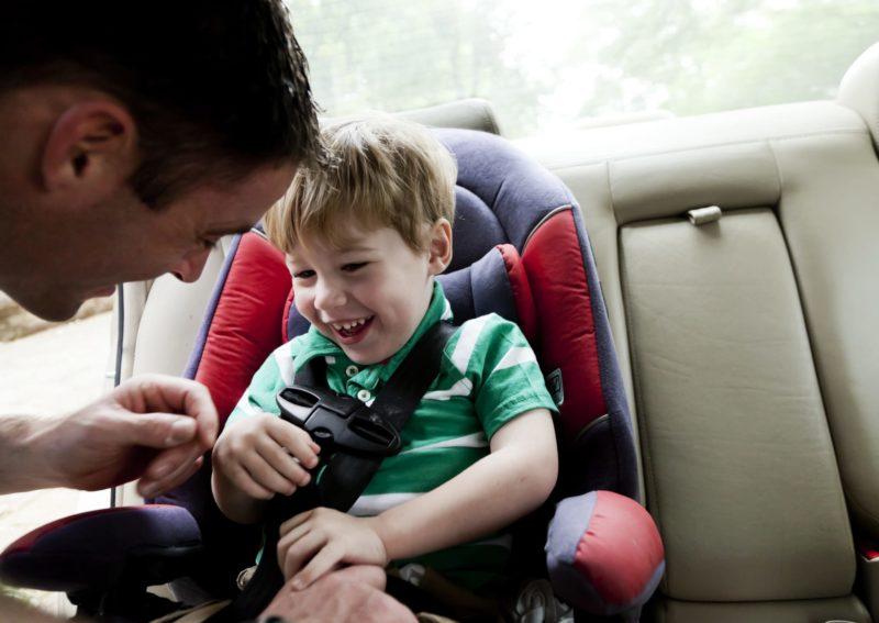 A father straps his son into a car seat.