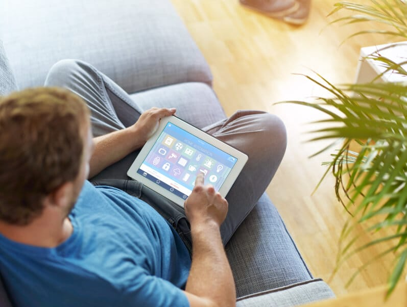 man on couch with tablet