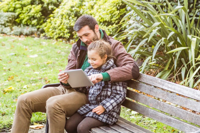 father and daughter on park bench looking at tablet