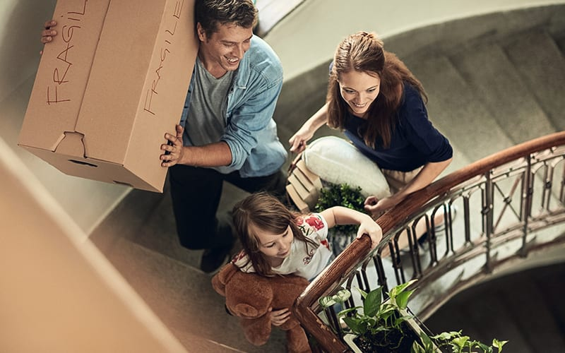 family walking up staircase with box