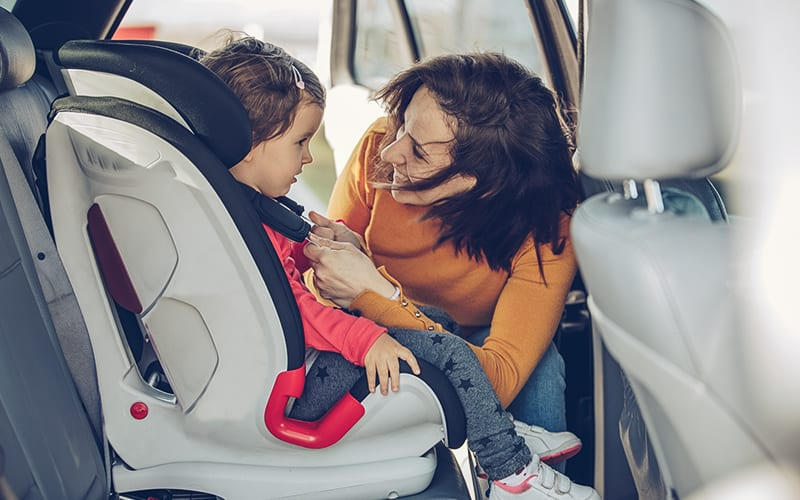 mother securing child in car seat