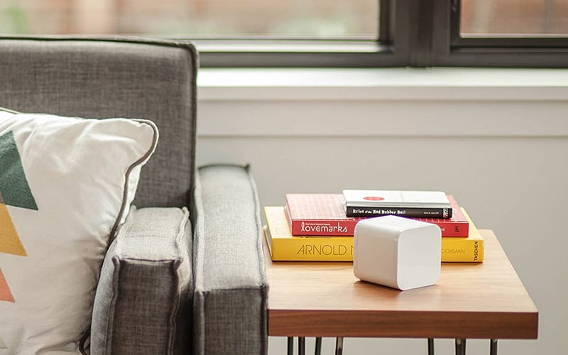 circle on wooden end table next to books and beside a grey chair with a pillow