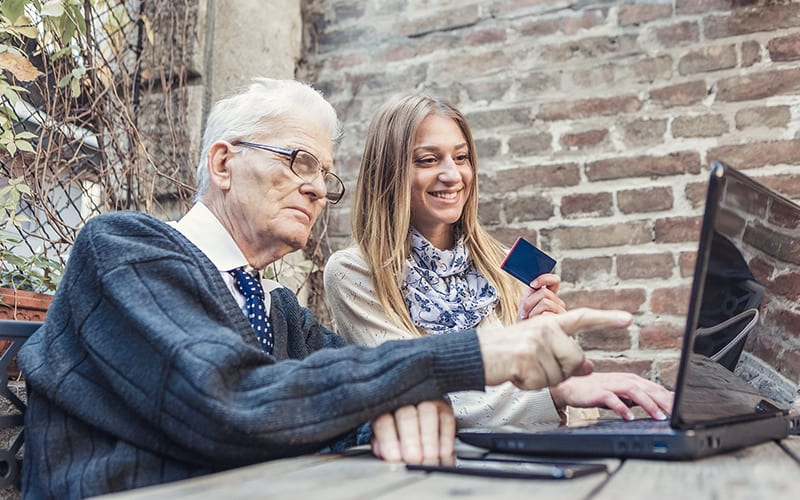 a senior citizen using a computer with young woman