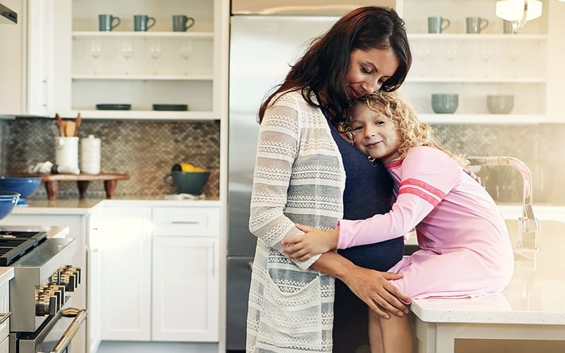 pregnant mom standing by kitchen counter with daughter hugging her belly
