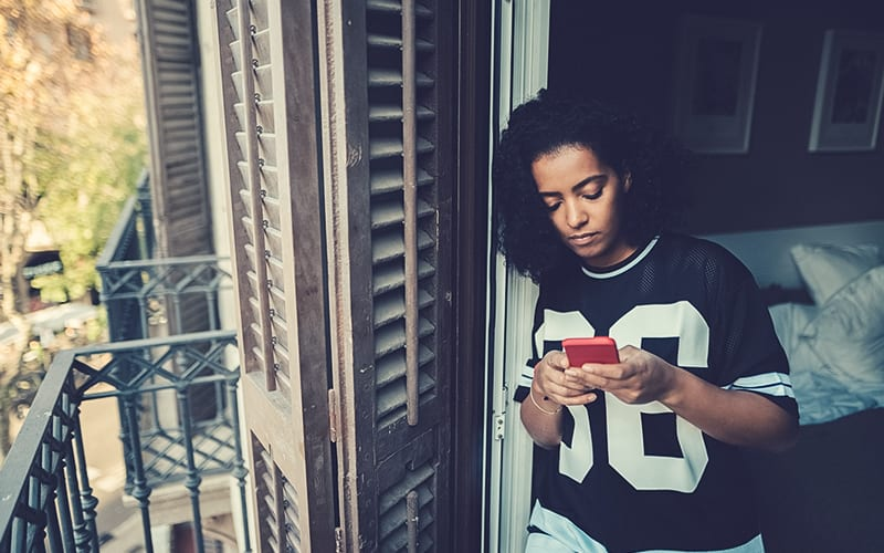 teenager on phone near balcony of house