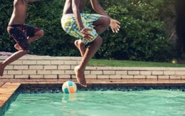 two kids jumping in pool