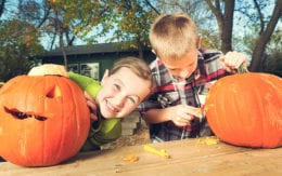 Boy and girl carving pumpkins
