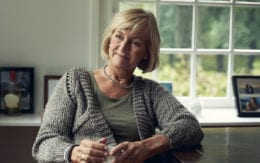 older woman in a sweater with a cup of coffee sitting in front of a window