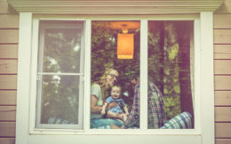 family with mom, dad, baby in window