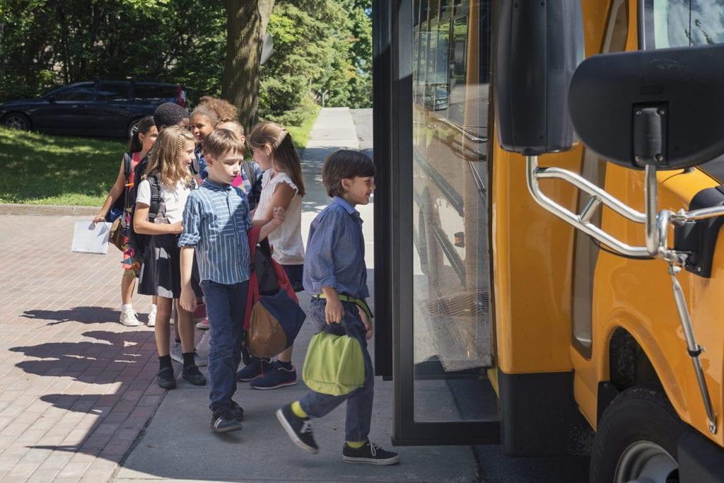 Group of elementary school kids getting in yellow school bus.