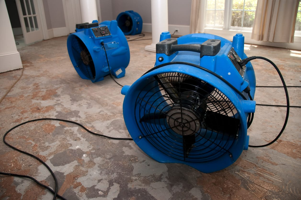 Large blue industrial fans in a flooded house on cement floor