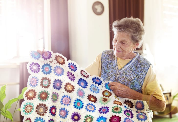 older woman holding up a crocheted afghan