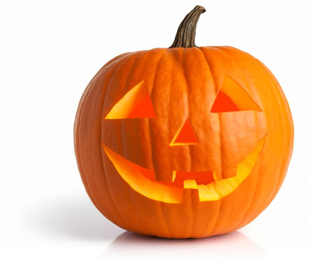Jack o' lantern aglow within isolated with shadow and reflection. Clipping path provided.
