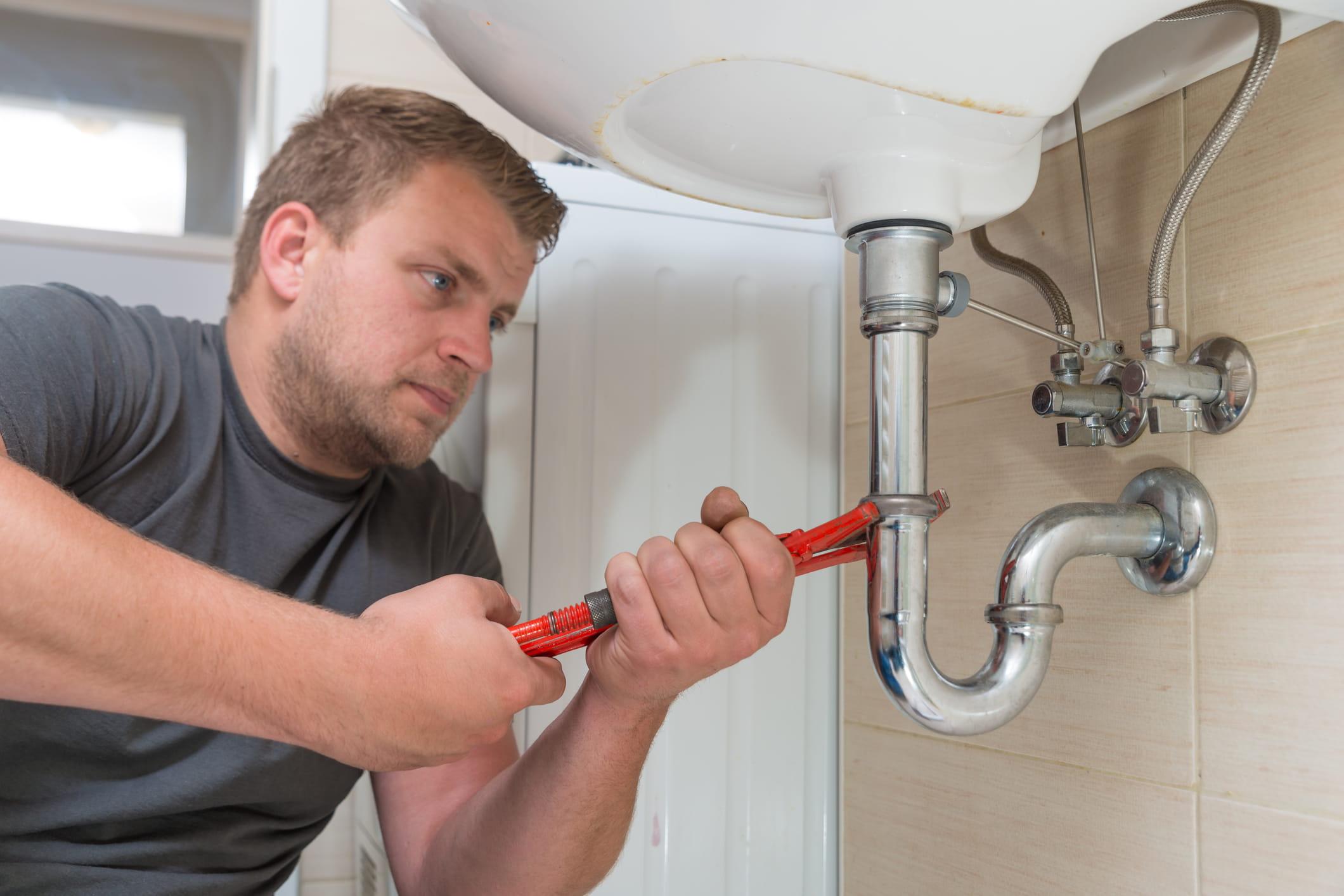 Photo of plumber repairing drain.