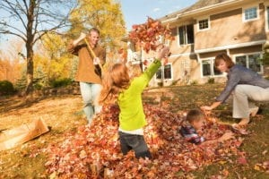 family playing in the leaves in fall