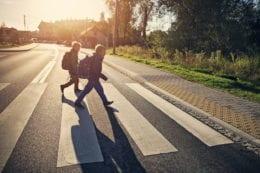 two school boys walking on zebra crossing on way to school.