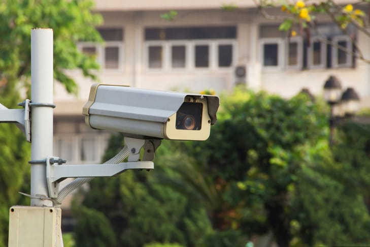 outdoor security camera with house and trees behind