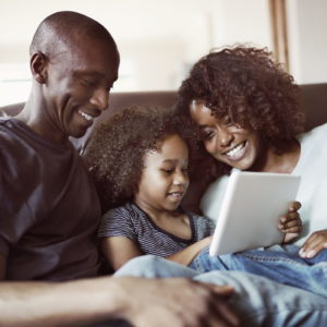 Happy parents looking at son using digital tablet