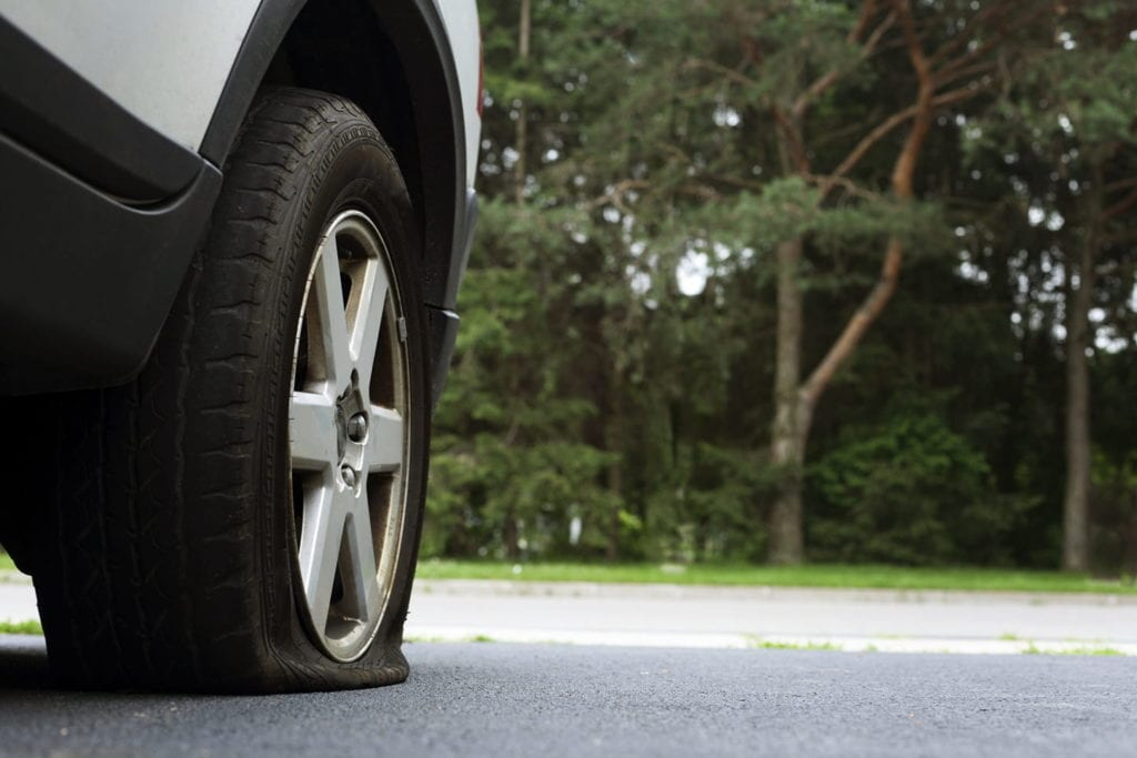 Close-up photo of a flat tire on a car on a road