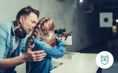 father showing daughter how to shoot rifle